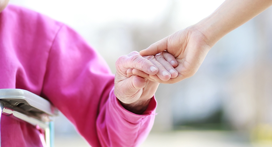 Image shows a carer's hand holding the hand of the person they care for