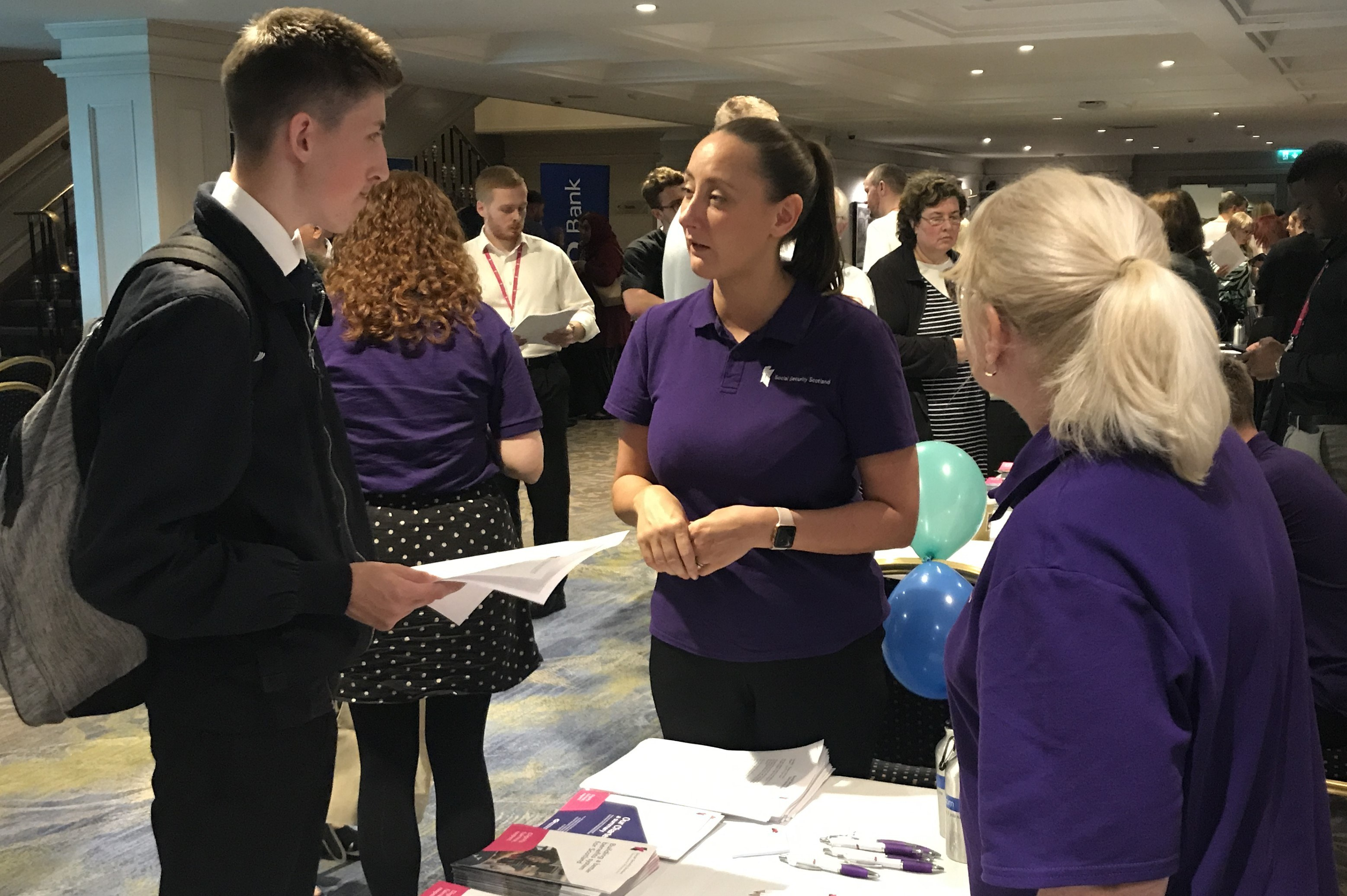 Image shows someone visiting a Social Security Scotland stall at a jobs fair