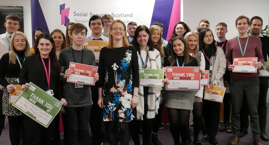 Group shot of Cabinet Secretary Shirley-Anne Somerville standing smiling with Modern Apprentices from Social Security Scotland