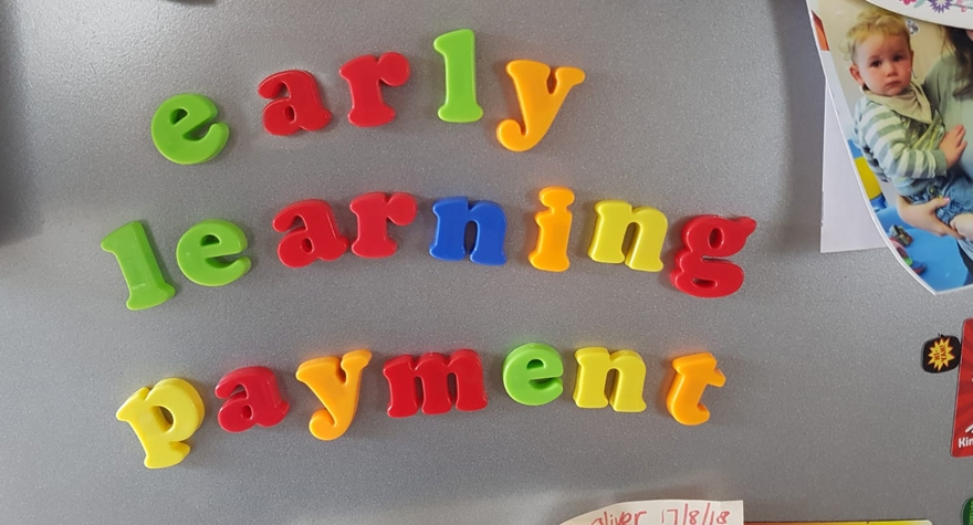Fridge magnets arranged to spell Early Learning Payment