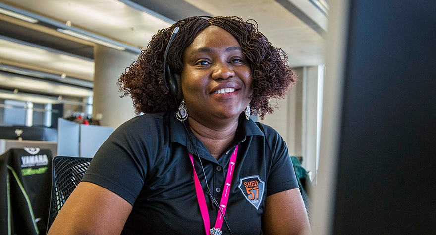 Image shows smiling woman with headset answering calls